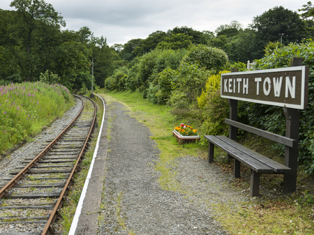 keith: Keith Town sign on empty bench by railroad track, Keith, Moray, Scotland Stock Photo