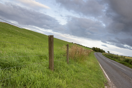 Country road passing through landscape against cloudy sky, St Andrews, Fife, Scotland
