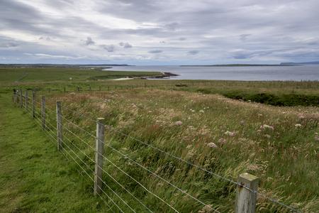 fencepost: Fence at coast against cloudy sky, John o Groats, Caithness, Scottish Highlands, Scotland Stock Photo