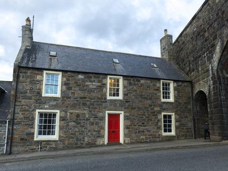entranceway: Facade of house with red door, Cullen, Moray, Scottish Highlands, Scotland Stock Photo