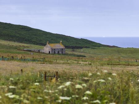 Abandoned house on grassy landscape at coast, Scottish Highlands, Scotland Stock Photo
