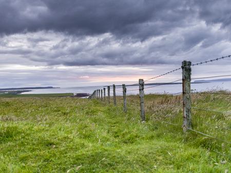 fencepost: Fence on landscape at coast against cloudy sky, John o Groats, Caithness, Scottish Highlands, Scotland