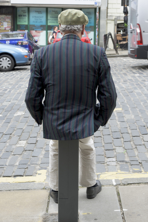 back view: Rear view of a senior man sitting on a post by the roadway, Frederick Street, Edinburgh, Scotland
