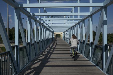 Woman cycling on Irene Hixon Whitney Bridge in Minneapolis, Hennepin County, Minnesota, USA
