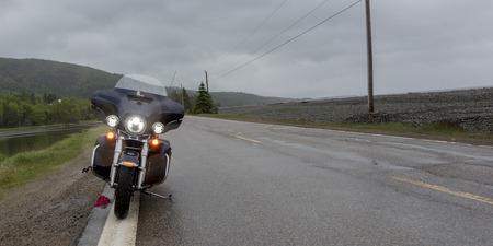 Motorrad parkte auf Straßenrand durch Fluss, Englishtown, Kap-Breton-Insel, Neuschottland, Kanada