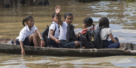 Students on their way to school by boat in Tonle Sap lake, Kampong Phluk, Siem Reap, Cambodia Editorial