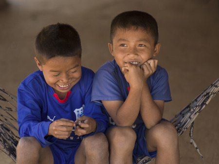 Happy boys sitting on a hammock, Ban Houy Phalam, Laos