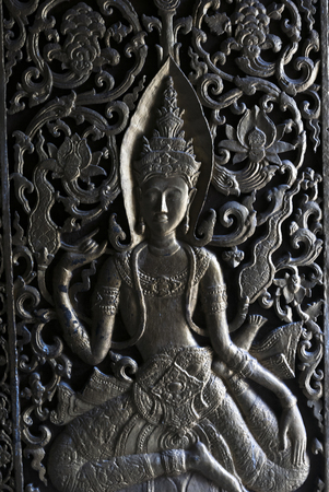 Female sculpture carved on door of temple, Luang Prabang, Laos