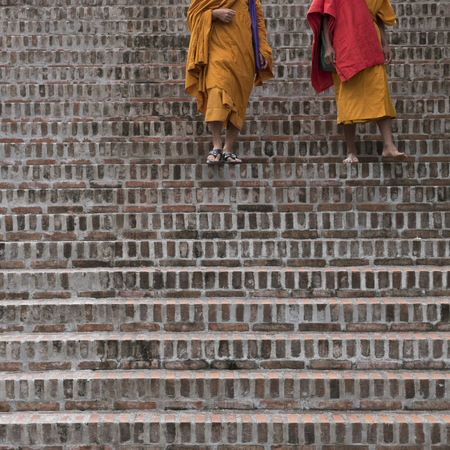 Monks walking down staircase, Luang Prabang, Laos Фото со стока