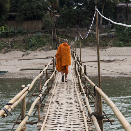 Monk walking on bamboo bridge over Nam Khan river, Luang Prabang, Laos Stock Photo