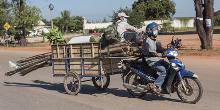 Motorcycle towing cart with cargo in Siem Reap, Cambodia Editorial