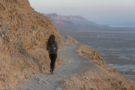 Rear view of teenage girl walking at abandoned fort, Masada, Judean Desert, Dead Sea Region, Israel Stock Photo