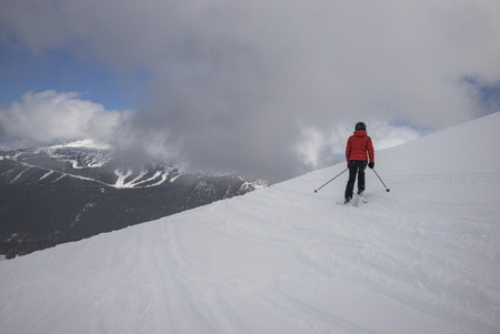 Tourist skiing on snowy mountain, Whistler, British Columbia, Canada