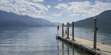 Tourists standing on pier in lake, Slocan Lake, Slocan Park, British Columbia, Canada Stock fotó