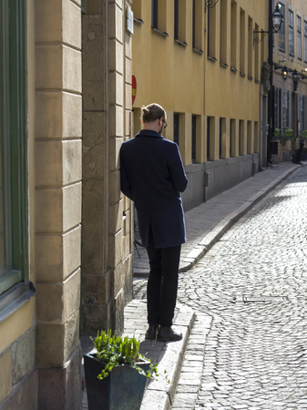 Rear view of man standing on sidewalk, Gamla Stan, Stockholm, Sweden Imagens
