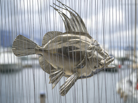Close-up of a metal sculpture of fish behind bead curtain, Montenegro