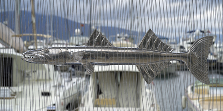 Close-up of a metal sculpture of barracuda fish behind bead curtain, Montenegro
