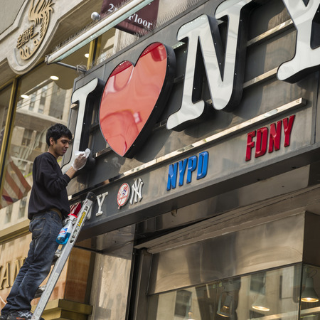 Man cleaning neon signs of store, Manhattan, New York City, New York State, USA