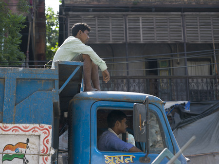 Two men riding on a truck, Kolkata, West Bengal, India