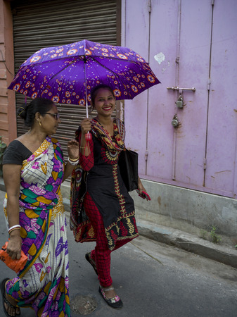 Two women walking with umbrella in alley, Kolkata, West Bengal, India