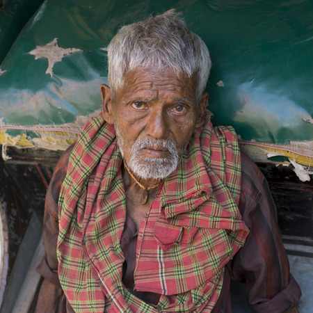 Elderly man leaning on hand-pulled rickshaw, Kolkata, West Bengal, India