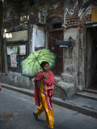 Woman walking with umbrella in alley, Kolkata, West Bengal, India