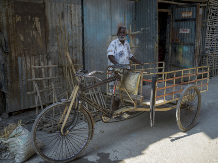 Elderly man standing near rickshaw, Kumartuli, Kolkata, West Bengal, India