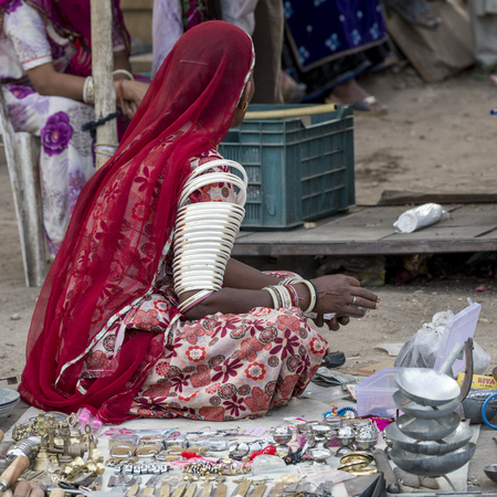 Woman in traditional attire selling craft products in street market, Jaisalmer, Rajasthan, India