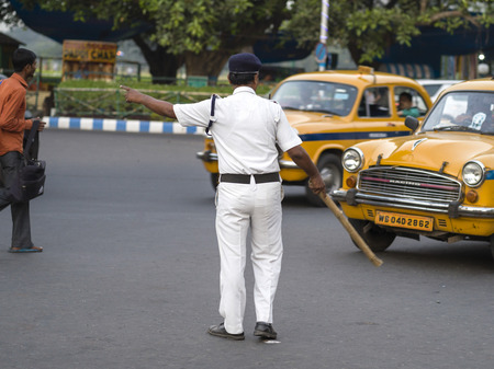 Police officer controlling traffic on street, Kolkata, West Bengal, India