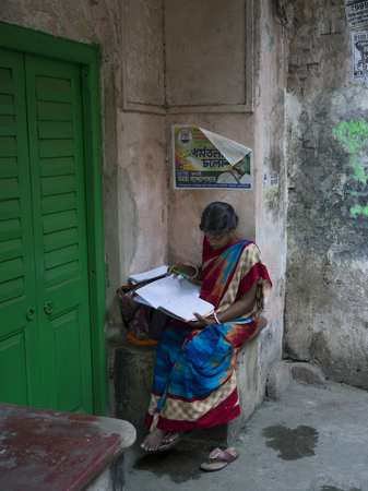 Woman reading a notebook, Kolkata, West Bengal, India
