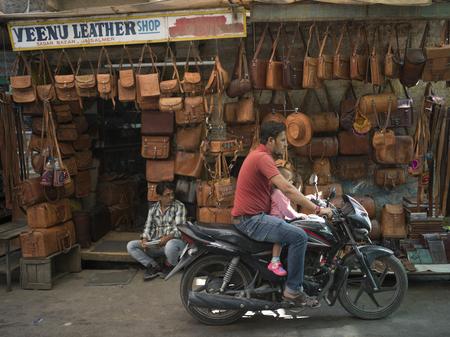 Man riding motorcycle in front of bag store, Sadar Bazar, Jaisalmer, Rajasthan, India