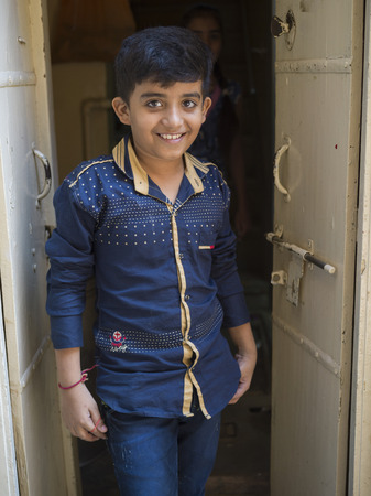 Happy boy standing at the entrance of room, Jaisalmer, Rajasthan, India