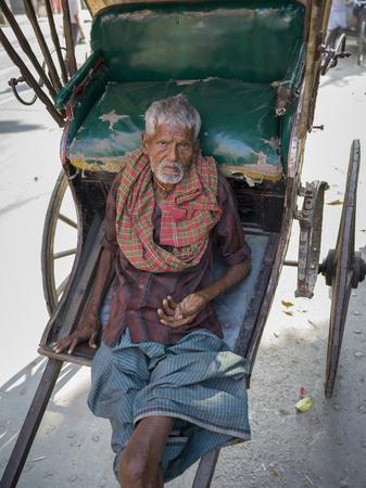 Elderly man leaning on hand-pulled rickshaw, Kolkata, West Bengal, India