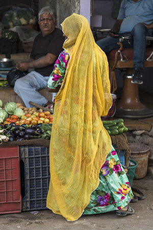 Woman in traditional attire buying vegetables from market stall, Jaisalmer, Rajasthan, India