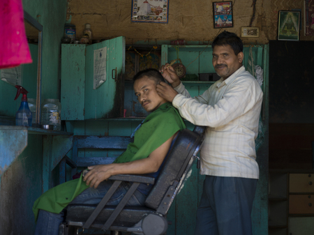 Man getting hair cut in barber shop, Kaluk, Sikkim, India
