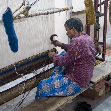 Man weaving carpet in a handloom, Jaipur, Rajasthan, India Редакционное