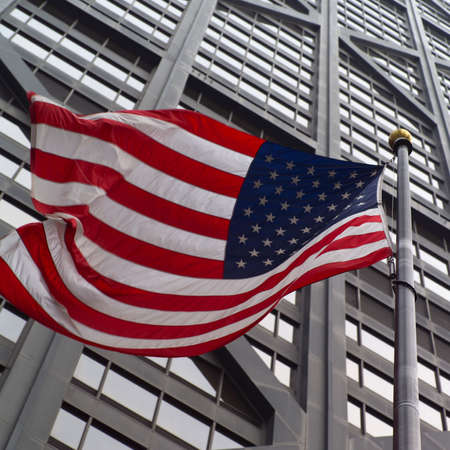 john hancock: Low angle view of the American flag outside John Hancock Building in Chicago