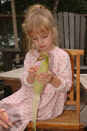 pealing: Small child pealing corn husk