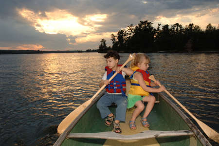 four year olds: Two four year olds holding oars in a boat Stock Photo