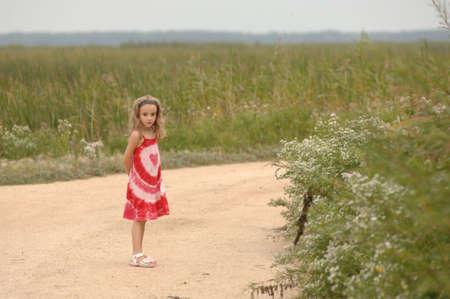 sundress: Girl in sundress standing on dirt road Stock Photo