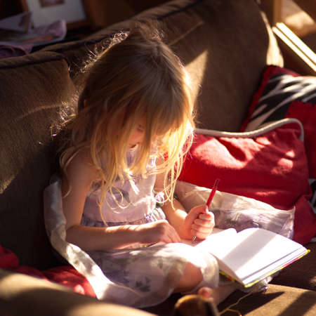throw cushion: 5 year old sitting on a sofa and writing in a book