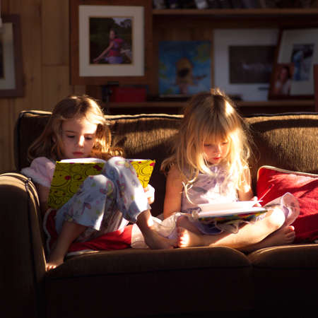 throw cushion: Two girls on a sofa looking at books Stock Photo