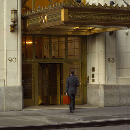 entranceway: Business man carrying a brief case entering a building, New York City Stock Photo