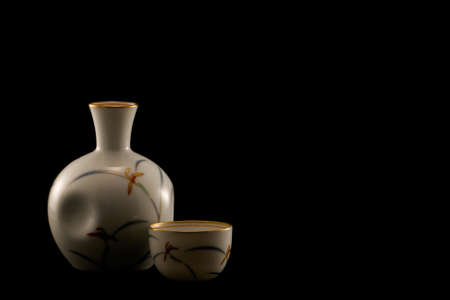 saki: japanese porcelain sake bottle and cups on a black background Stock Photo