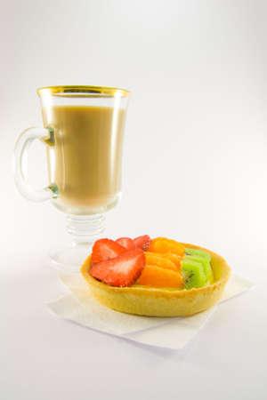 Strawberry, mandarin and kiwi custard fruit tart on a napkin with latte on a  white background Stock Photo - 4667699