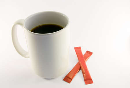 sachets: Taza de caf� de altura de color blanco con dos sobres de az�car de color rojo sobre fondo blanco Foto de archivo