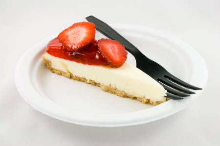 Slice of strawberry chessecake with a black fork on a white plate with a white background Stock Photo - 4802068