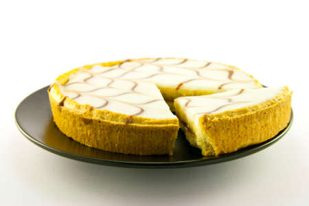 jam tarts: delicious looking iced bakewell tart on a black plate with a plain background