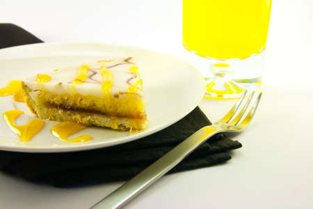 treacle: delicious looking iced bakewell tart on a black plate with a treacle drizzle and a fork on a plain background