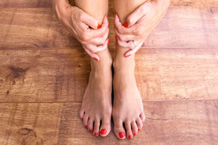Feet placed on a wooden background with hands holding ankles photo